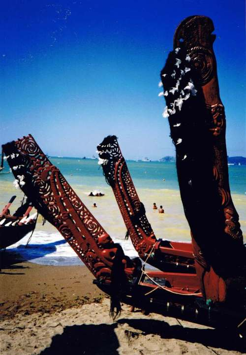 Carved sternposts of beached 'waka' (canoes) on the beach near Waitangi.